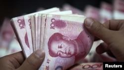 國營中國工商銀行在安徽某儲蓄所的職員點算人民幣百元鈔票。 (資料圖片)