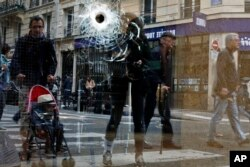 A bullet hole is seen on the window of a cafe located near the area where the assailant of a knife attack was shot dead by police officers, in central Paris, France, May 13, 2018.