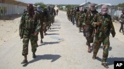 FILE - Members of Somalia's al-Shabab militant group patrol on foot on the outskirts of Mogadishu, March 5, 2012. Somalia now says al-Shabab militants are plotting to supply uranium to Iran.