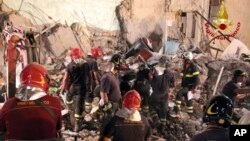 Firefighters search amid rubble of a collapsed apartment in Torre Annunziata, near Naples, Italy, July 8, 2017. Italian firefighters say eight bodies have been pulled from the rubble of a five-story apartment building that partially collapsed in a seaside town south of Naples.