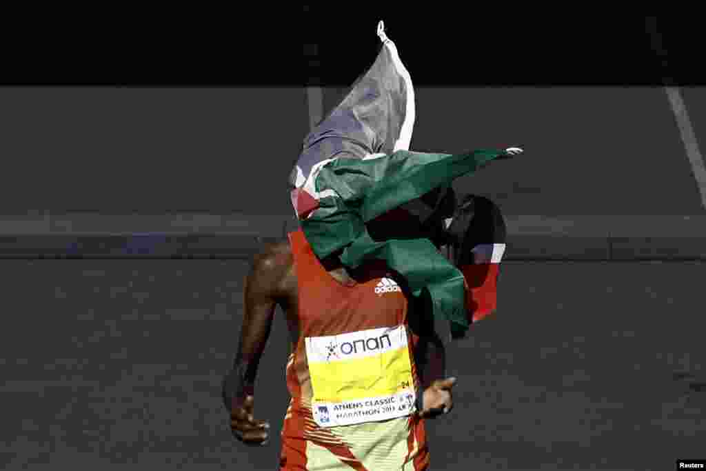 Kenya's Hillary Kipkogei Yego crosses the finish line to win the men's race of the 31st Athens Classic Marathon as a flag thrown by a fan covers his face at the Panathenaic stadium in Athens, Greece.
