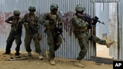FILE - Masked Somali national army (SNA) soldiers search through homes for al-Shabab fighters, during an operation in Ealsha Biyaha, Somalia, June, 2, 2012.