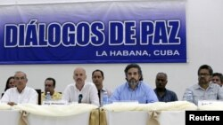 Colombia's lead government negotiator Humberto de la Calle (L) and Colombia's FARC lead negotiator Ivan Marquez (R) sit as mediators Dag Nylander of Norway (2nd L) and Rodolfo Benitez of Cuba read a joint declaration in Havana, July 12, 2015.