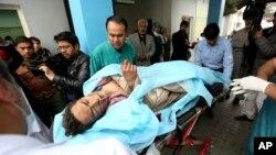 Người dân Afghanistan giúp đỡ một người đàn ông bị thương tại một bệnh viện sau vụ đánh bom tự sát ở Kabul, Afghanistan, ngày 21/11/2016.