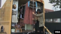 Jessie Goldenberg unloads goods from her mobile store.