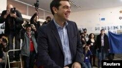 ທ່ານ Alexis Tsipras ຜູ້ນຳພັກຝ່າຍຄ້ານ ນິຍົມຊ້າຍ ຫົວຍິ້ມກ່ອນປ່ອນບັດ ທີ່ໜ່ວບປ່ອນບັດແຫ່ງນຶ່ງ ໃນນະຄອນຫຼວງ Athens ວັນທີ 25 ມັງກອນ 2015.