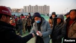北京一處建築工地裡一個工頭給工人發工資。(2021年2月6日)