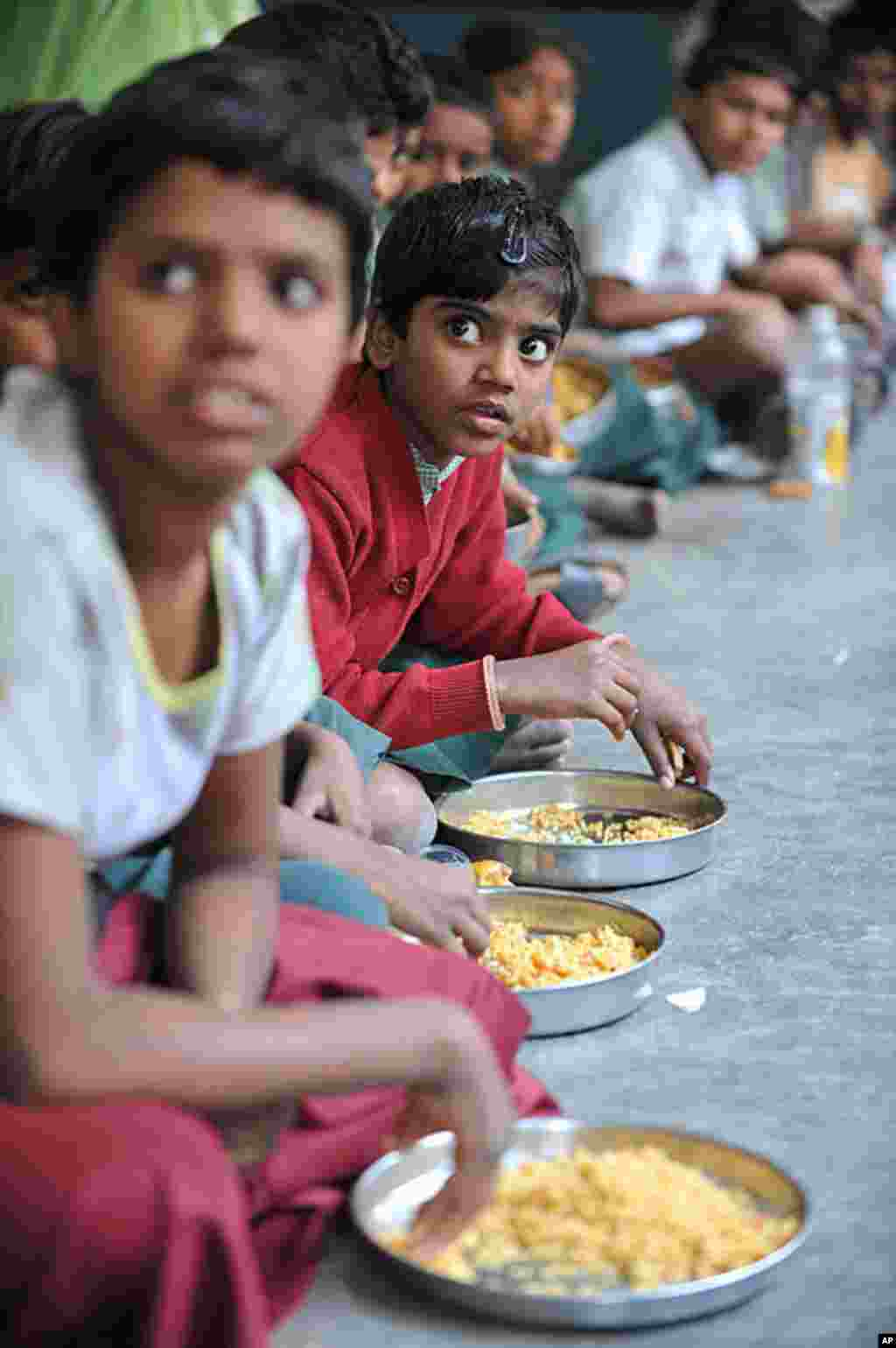 "Indian children eat their mid-day meal at an Government High School in Hyderabad. Levels of under-nutrition in the country were ""unacceptably high"" despite impressive GDP growth, Prime Minister Manmohan Singh said on January 10, 2012. (AFP)"