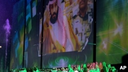 In this file photo taken Saturday Sept. 23, 2017, Saudi men perform under a giant screen showing an image of Saudi Crown Prince Mohammed Bin Salman during National Day ceremonies, at the King Fahd Stadium in Riyadh, Saudi Arabia. (Saudi Press Agency via AP)