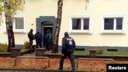 جرمن پولیس کے اہل کار ایک مشتبہ جہادی کی گرفتاری کے لیے اس کے گھر کے باہر کھڑے ہیں۔8 نومبر 2016