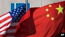 FILE - The flags of the United States and China flutter in winds outside a hotel in Beijing.