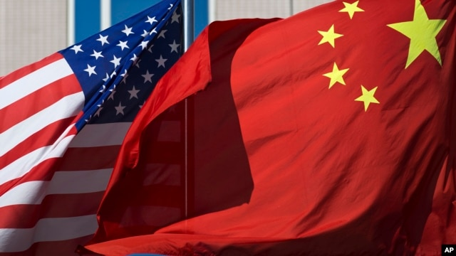 FILE - U.S. and Chinese flags flutter outside a hotel in Beijing, Sept. 5, 2012.