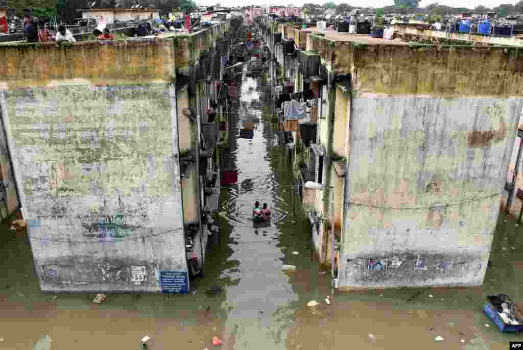 People gather around a residential area that was flooded after heavy rains in Chennai, India.