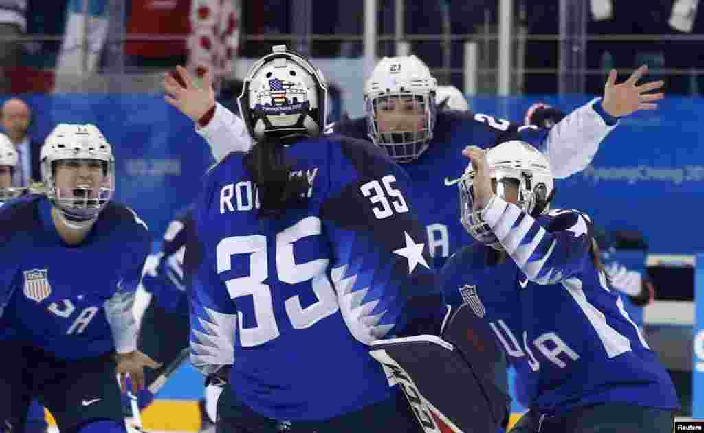 U.S. players celebrate with teammate and goalie Maddie Rooney after she made the winning save in the women's gold medal hockey game in Gangneung, South Korea, Feb. 22, 2018.