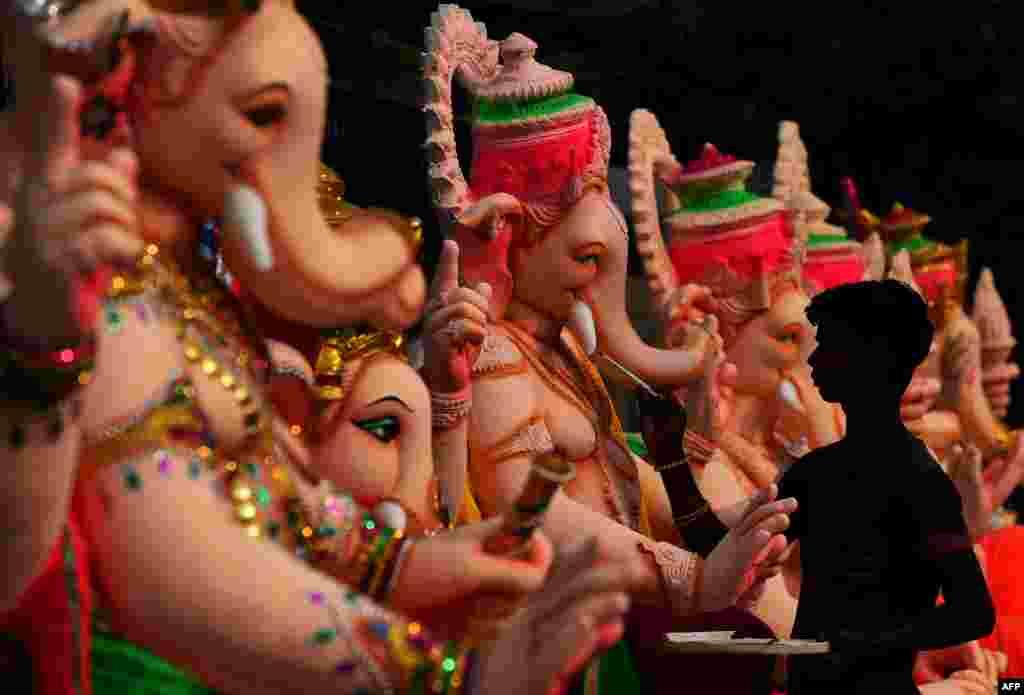 សិល្បករឥណ្ឌាម្នាក់បង្ហើយការបន្ថែមពណ៌ទៅលើរូបចម្លាក់ព្រះគិណេស នៃសាសនាហិណ្ឌូ នៅឯរោងជាងមួយ នៅមុនពិធីបុណ្យ Ganesh Chaturthi ដែលឧទ្ទិសដល់ព្រះគិណេស នៅក្នុងរដ្ឋធានីញូដេលី (NewDelhi) ។