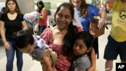 Buena Ventura Martín-Godínez, (centro), sostiene a suh hijo Pedro, (izquierda) cuando se reúne con su hija Janne, (derecha), en el Aeropuerto Internacional de Miami, el domingo 1 de julio de 2018. Martín ingresó ilegalmente a EE.UU. desde México en mayo con su hijo huyendo de la violencia en Guatemala. Su esposo cruzó dos semanas después con Janne. Todos fueron capturados por la patrulla fronteriza y separados. La niña fue liberada el domingo de una agencia de bienestar infantil en Michigan. (AP Photo/Lynne Sladky)