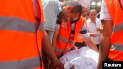 Pristalica svrgnutog egipatskog predsednika plače nad telom svog rođaka, koga pripadnici hitne pomoći iznose iz poljske bolnice u blizini mesta sukoba policije i pro-Morsjevihi demonstranata u oblasti Nasr Siti, u Kairu