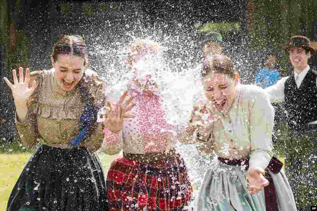 Women in traditional costumes are sprayed with water as members of the Marghareta Dance Group perform Easter folk traditions of the region in the Museum Village in Nyiregyhaza, northeast of Budapest, Hungary.