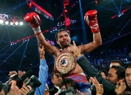Manny Pacquiao from the Philippines wears the champion's belt after defeating Brandon Rios of the United States in the WBO international welterweight title fight, Nov. 24, 2013, in Macau.