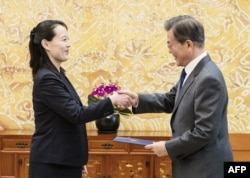 FILE - North Korean leader Kim Jong Un's sister Kim Yo Jong hands an autographed letter from Kim Jong Un to South Korea's President Moon Jae-in during their meeting at the presidential Blue House in Seoul, Feb. 10, 2018.