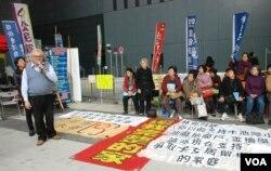 甘浩望神父(左一)帶領超過30名港人大陸超齡子女的家長,在政府總部外靜坐