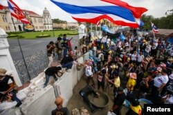 Anti-government protesters mix cement to be used for building a wall to block a gate of the Government House during a rally in Bangkok, Feb. 17, 2014.
