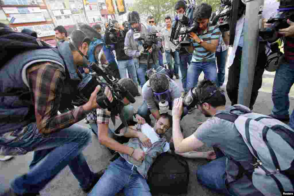 An injured journalist is filmed and helped by his colleagues during clashes between riot police and May Day protesters in central Istanbul, Turkey.