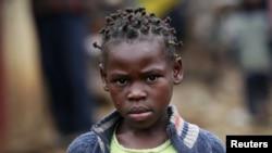 Một bé gái đi bộ qua một con phố trong khu ổ chuột Kibera tại Nairobi, Kenya.