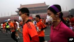 2014年10月19日,北京受到霧霾天氣影響,國際馬拉松賽的參加者戴口罩在霧霾中跑步。