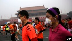 参加北京国际马拉松长跑的人在雾霾中跑过天安门,有些人带着口罩(2014年10月19日)