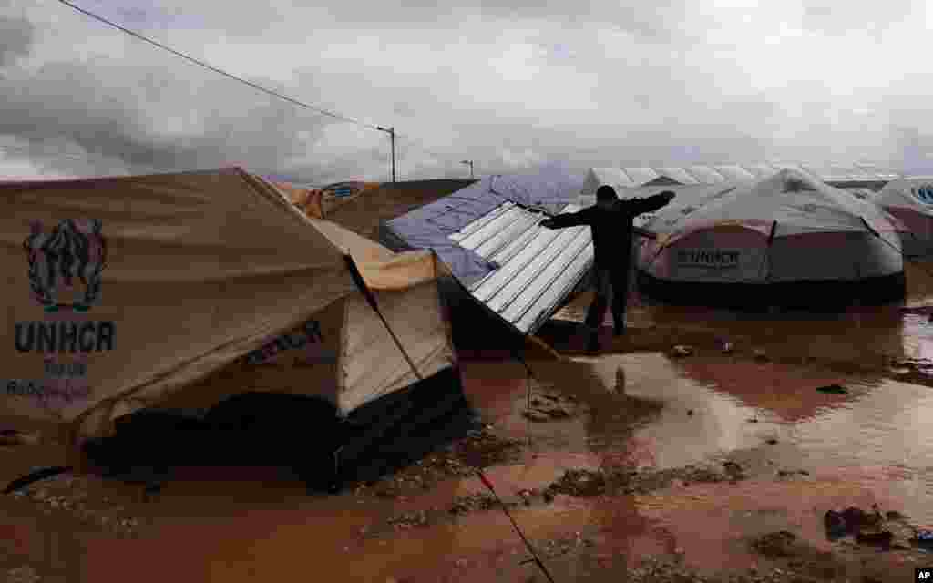 A Syrian refugee man jumps to avoid muddy water near his tent, at Zaatari refugee camp, near the Syrian border in Mafraq, Jordan, January 9, 2013.