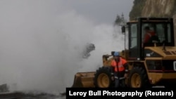 A wave hits heavy machinery as emergency personnel work on a flooded road in Nelson, after the downgraded Cyclone Fehi brought heavy rain in New Zealand, Feb. 1, 2018.