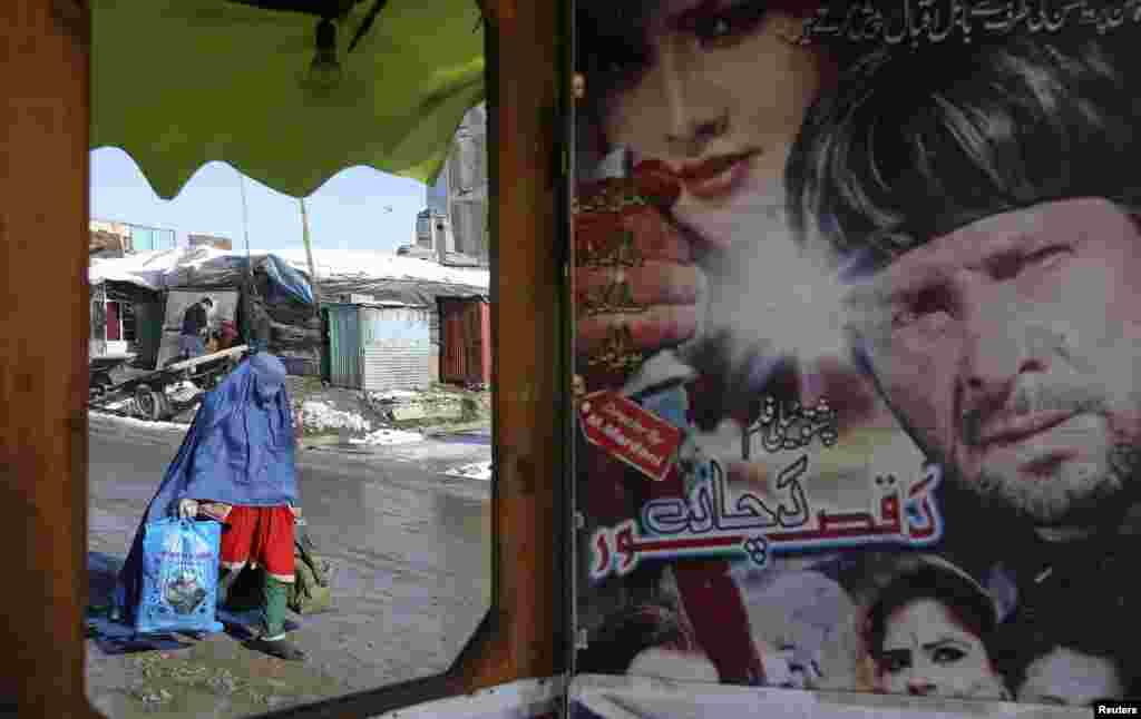 An Afghan woman is reflected in a mirror at a small music shop in Kabul.