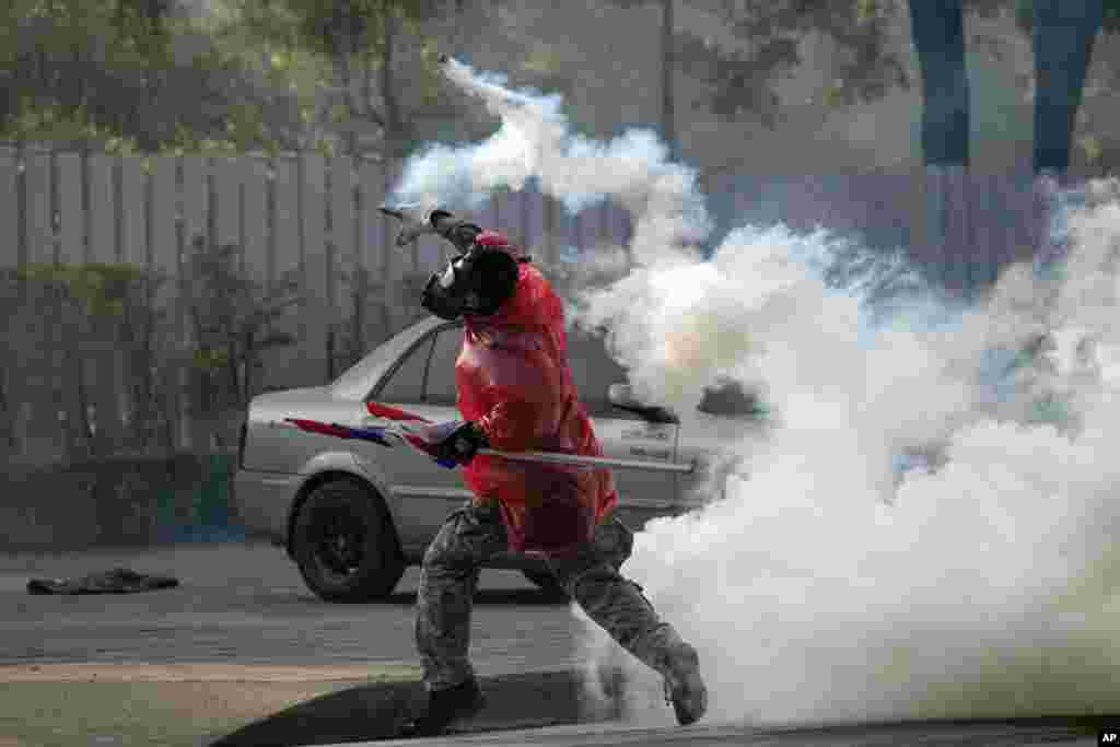 An anti-government protester throws back a tear gas canister at riot police during a clash at a sport stadium in Bangkok, Dec. 26, 2013.