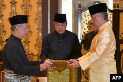 Perdana Menteri Malaysia Muhyiddin Yassin (kiri) menerima dokumen dari Raja Sultan Abdullah Sultan Ahmad Shah (kanan). (Foto: AFP)
