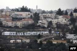 FILE - This photo taken on January 25, 2017 shows a partial view of the Israeli settlement of Beit El near the West Bank city of Ramallah (background).