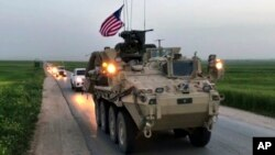 This Friday, April 28, 2017 still taken from video, shows U.S. forces patrolling on a rural road in the village of Darbasiyah, in northern Syria.
