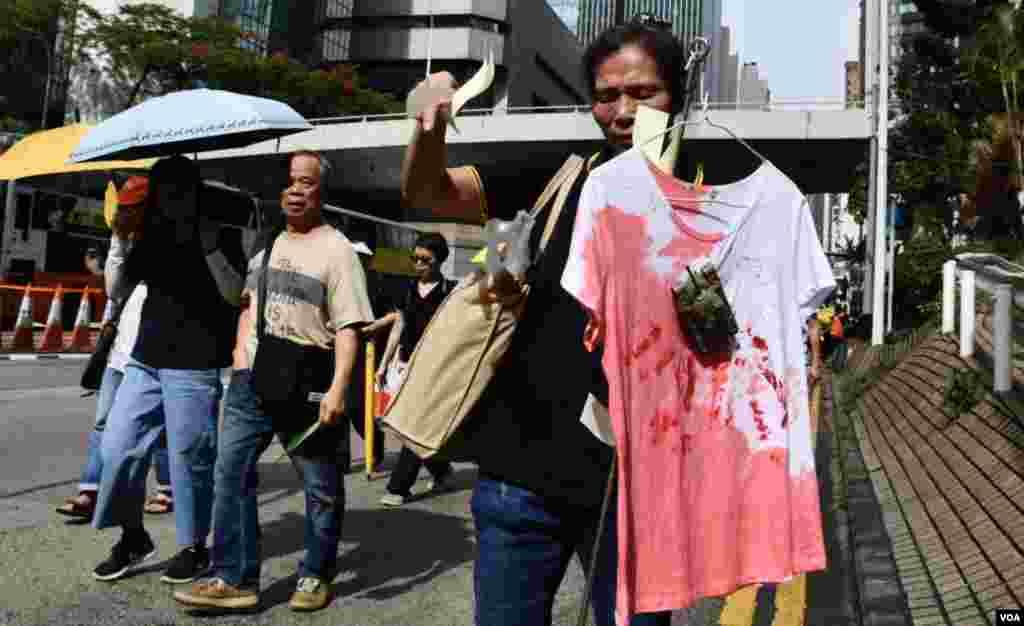 遊行人士手持一件象徵染血的T恤,沿途撒冥紙悼念六四死難者。(美國之音湯惠芸攝)