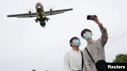 两名戴着口罩的青年正在以即将降落在台湾台北松山机场的飞机做背景自拍。(2020年3月29日)
