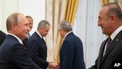 Russian President Vladimir Putin, left, shakes hands with Turkish Foreign Minister Mevlut Cavusoglu during their meeting in the Kremlin in Moscow, Russia, Aug. 24, 2018.