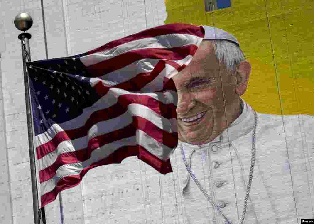 A bandeira dos EUA agitada pelo vento em frente à imagem do Papa Francisco num mural de um edifício em Manhattan, Nova Iorque, Agosto. 28, 2015.