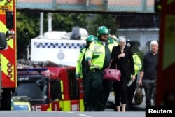 An injured woman is led away after an incident at Parsons Green underground station in London, Britain, Sept. 15, 2017.