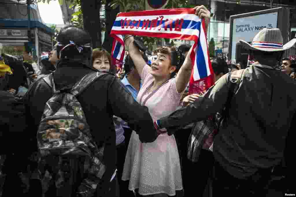 A reacção de uma manifestante contra o Governo, enquanto o líder Suthep Thaugsuban (não se vê na imagem) conduz a marcha na zona financeira de Banguecoque, Jan. 23, 2014.