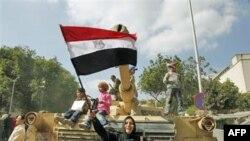 Một người biểu tình vẫy cờ Ai Cậo trước chiếc xe tăng của quân đội tại Quảng trường Tahrir Square ở Cairo, ngày 12 tháng 2, 2011