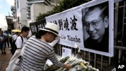 14일 홍콩의 중국 연락사무소 앞에 시민들이 류샤오보를 추모하는 꽃과 메시지를 남기고 있다.
