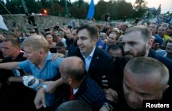 FILE - Former Georgian President Mikheil Saakashvili is surrounded by his supporters as he arrives at a checkpoint on the Ukrainian-Polish border in Shehyni, Ukraine, Sept. 10, 2017.
