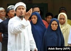 Ulama Dzulkarnain (kiri) meneriakkan slogan-slogan di samping Tariyem (kedua dari kanan) ibu dari terpidana pelaku bom Bali 2002 Amrozi dan Mukhlas, dan dua saudara perempuan (belakang) dalam kunjungan mendukung tiga pelaku bom Bali di Tenggulun pada 6 No