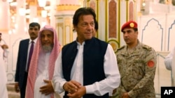 In this Tuesday, Sept. 18, 2018, photo released by the state-run Saudi Press Agency, Pakistani Prime Minister Imran Khan, center, visits the Prophet's Mosque in Medina, Saudi Arabia. Khan, a former cricketer, is on a tour of Saudi Arabia and the United Arab Emirates as part of his first overseas trip since taking office.