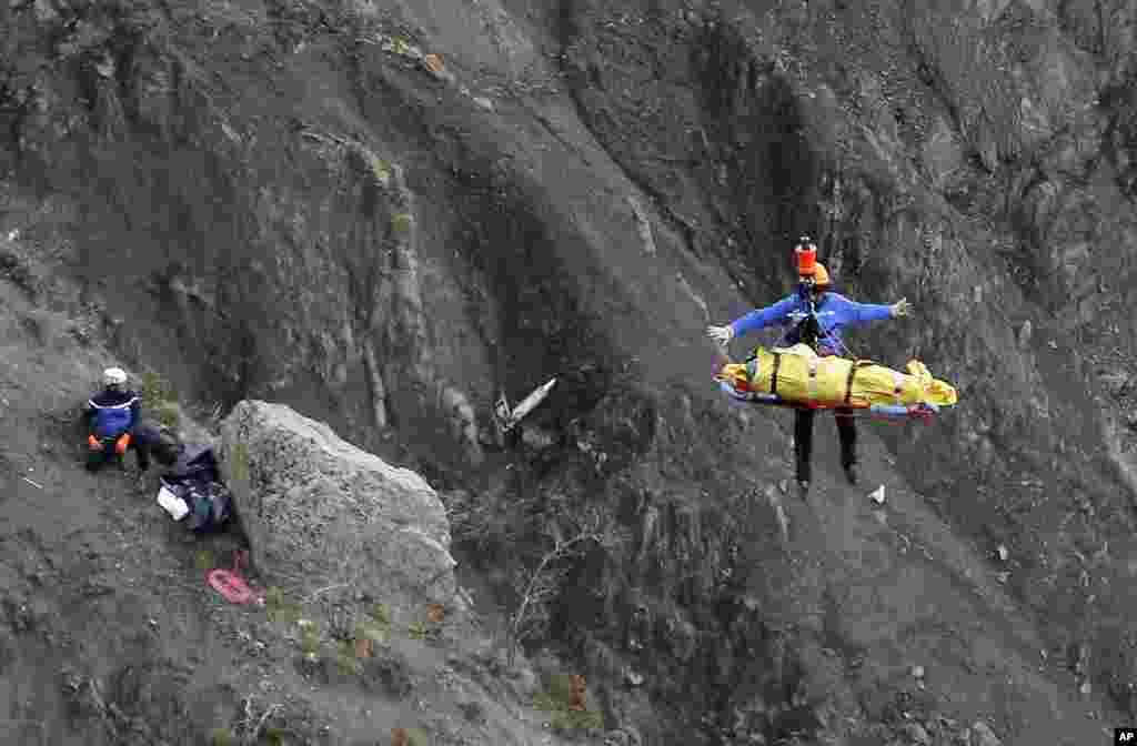 A rescue worker is lifted into an helicopter at the crash site near Seyne-les-Alpes, France, . The co-pilot of the Germanwings jet barricaded himself in the cockpit and internationally rammed the plane full speed into the French Alps, ignoring the captain's frantic pounding on the cockpit door and the screams of terror from passengers, a prosecutor said.