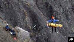 Seorang petugas penyelamatan diangkat ke dalam helikopter di lokasi jatuhnya pesawat dekat Seyne-les-Alpes, Perancis (26/3). (AP/Laurent Cipriani)